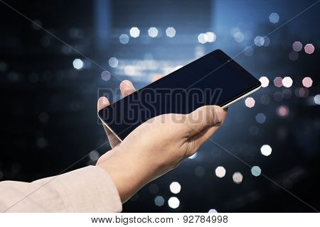 Hand Holding Cellphone With Blank Screen On Blurry Night City