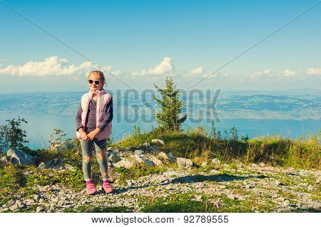 Cute little girl resting on the top of the mountain