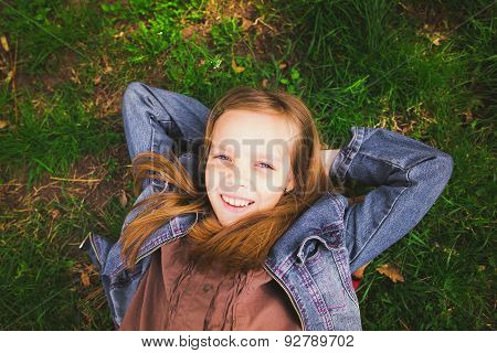 Portrait Of Young Girl Laying On Grass Outdoors