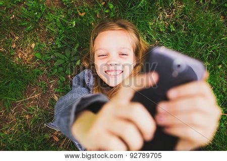 Girl Laying On Grass With Mobile Phone