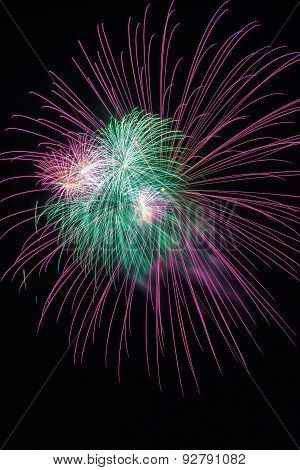 Green and violet amazing fireworks isolated in dark background