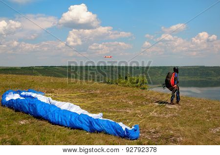Paraglider Prepares To Fly Over Beautiful Bakota Reservoir.