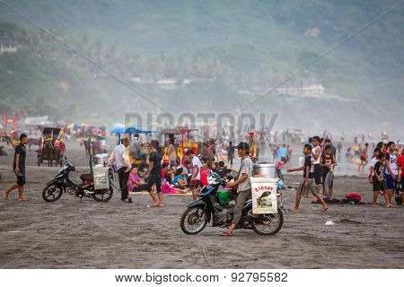 Food vendors and tourists on the black sand Parangtritis beach in Java, Indonesia