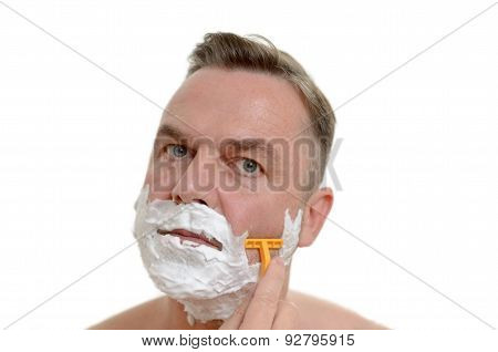 Man Shaving His Beard With A Razor And Lather