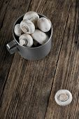 foto of champignons  - Vertical photo of old aluminum cup full of harvested mushrooms champignons on old wooden board with single one out of pile - JPG