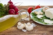 image of champignons  - Horizontal photo of Champignons and various vegetable radishes tomatoes) with coarse-grained salt around plus bottle with lemonade. All is on wooden table.