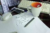 pic of draft  - Draft of a business plan on a paper computer mug and mobile phone in the background - JPG