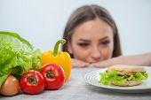 stock photo of hamburger  - Beautiful young girl is looking at the hamburger with appetite - JPG