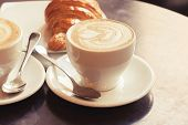 Постер, плакат: Cappuccino With Croissant Two Cups Of Coffee On Table