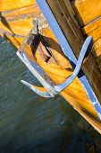 stock photo of old boat  - Metallic Shining Boat Anchor On a Wooden Old Boat