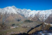 stock photo of greater  - Aerial view on Gergeti village and Stepantsminda town in Greater Caucasus Range Georgia - JPG