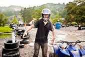 image of mud  - young boy is facinated by quad driving  - JPG