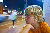 pic of boys night out  - cute boy smiles tired while sitting outside by night next to the street - JPG