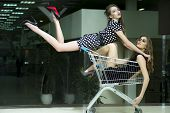 picture of black heel  - Horizontal picture with two young winning sexy unusual girls with bright makeup and beautiful slim legs where one in short dress with white polka dots and black red shoes high heels with flowing straight hair jumped and luing on cart with a girl sitting i - JPG
