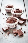 stock photo of chocolate muffin  - Chocolate muffins decorated with mint leaves and chocolate chips on a wooden table - JPG