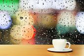 stock photo of raindrops  - coffee cup on the background of the window with raindrops - JPG