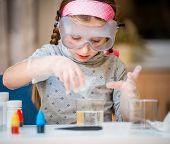 stock photo of little school girl  - happy little girl with flasks for chemistry - JPG