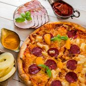 picture of exotic_food  - exotic pizza with pineapple and peach with food ingredients on a wooden table - JPG