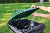 stock photo of throw up  - Close up hand throwing empty plastic bottle into the trash - JPG