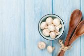 stock photo of champignons  - Fresh champignon mushrooms on blue wooden table with copy space - JPG