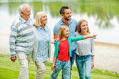 stock photo of girl walking away  - Happy young family walking outdoors together while little girl pointing away and smiling - JPG