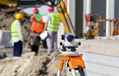 picture of theodolite  - Surveying measuring equipment level theodolite on tripod at construction site with workers in background - JPG