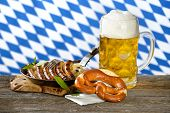 picture of pretzels  - Fried Nuremberg sausages on sauerkraut with a mug of Bavarian beer and a pretzel - JPG