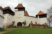 stock photo of fortified wall  - Medieval fortified church surrounded by defence walls - JPG
