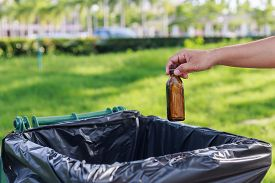 picture of segregation  - Close up hand throwing empty glass bottle into the trash - JPG