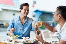 foto of cafe  - Tourist Men Cheers Toast Drink - JPG