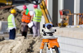 image of geodesic  - Surveying measuring equipment level theodolite on tripod at construction site with workers in background - JPG