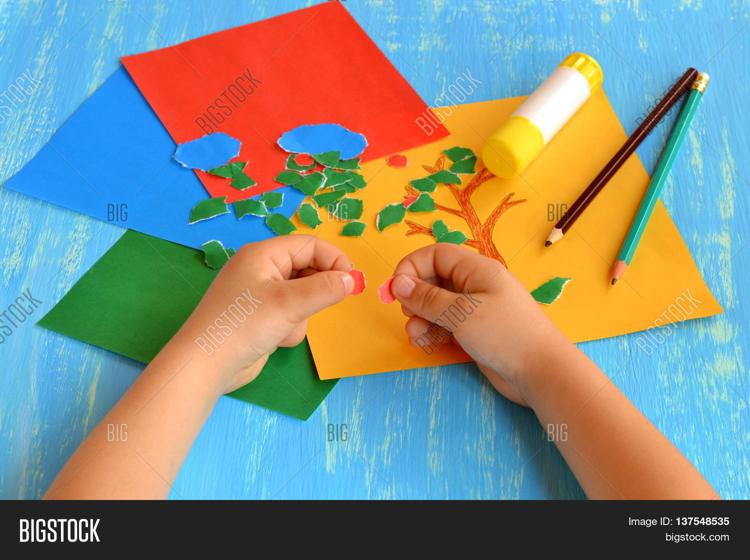 Tear fall colored construction paper into small pieces and glue - Child Tears A Red Paper Into Small Pieces Child Holds Colored Paper In His Hands