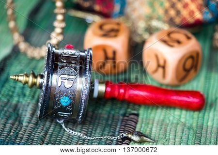 A Tibetan Prayer Wheel to increase good and get rid of bad karma laying on the table with dice