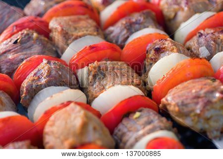 Close-up of pork meat pieces being with onion and tomatoes fried on a charcoal grill