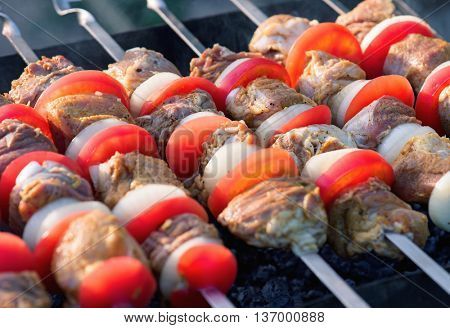 Pork meat pieces being with onion and tomatoes fried on a charcoal grill