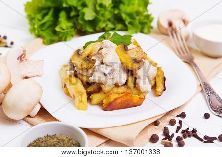 Fried potatoes with gravy of mushrooms in a plate on wooden background