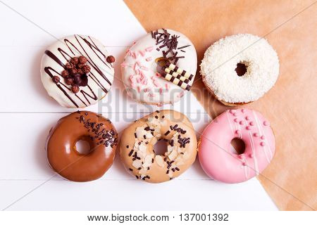 Six colored donuts with sprinkles on a white wooden background