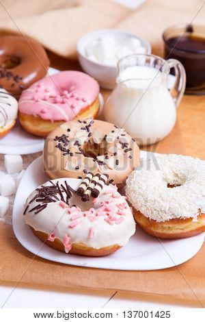 Colored donuts with glaze coffee and milk on a white wooden background
