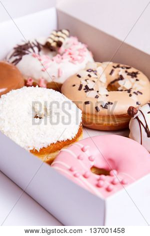 Colored donuts with sprinkles in a box on a white wooden background