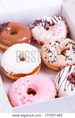 Colored donuts with sprinkles and glaze in a box