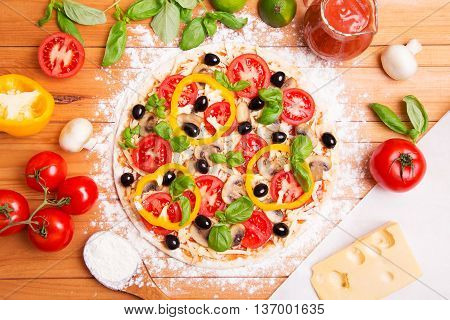 Prepared Italian pizza with sause tomato and other ingredients other on the wooden background