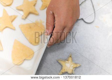 Homemade baking kitchen scene showing child holding baking tray with cut shortbread biscuits on baking paper ready to be cooked.