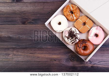 Colorful delicious donuts with coconut chocolate and other sprinkles in a box on a dark wooden background. Top view with copy space