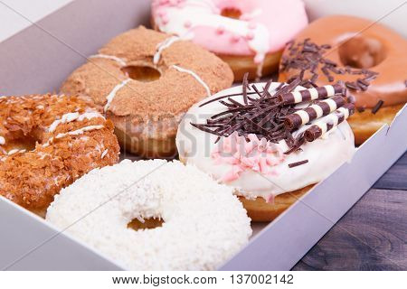 Colorful delicious donuts with glaze and sprinkles in a box on a dark wooden background