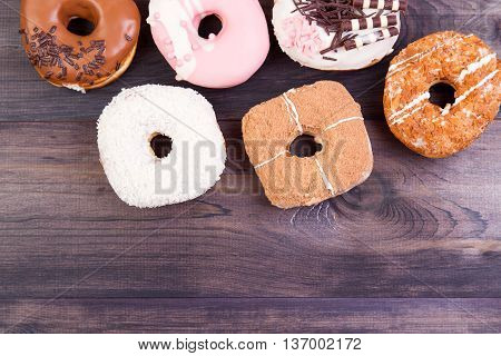 Colorful delicious donuts with chocolate coconut and other sprinkles on a dark wooden background. Top view with copy space