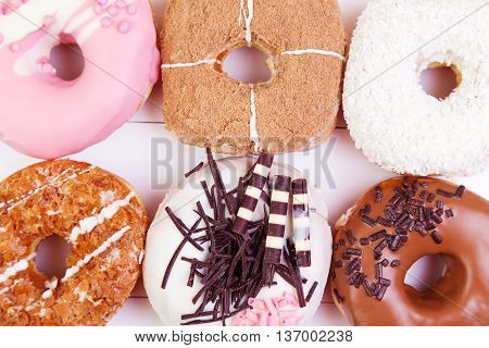 Colored delicious donuts with chocolate coconut and other sprinkles on a wooden background