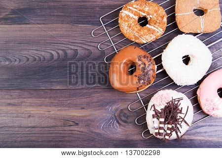 Colored delicious donuts with coconut and other sprinkles on a dark wooden table. Top view with copy space