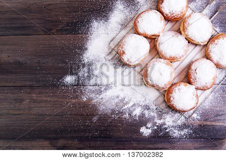 German donuts - berliner with icing sugar on a dark wooden background. Top view with copy space