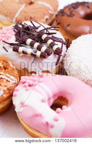 Colorful delicious donuts with glaze and sprinkles on a white wooden background