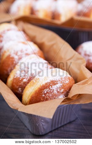 German donuts - berliner with jam and icing sugar in a box on a dark wooden table